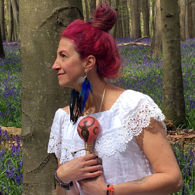 Gloria Urech in woods holding a maraca