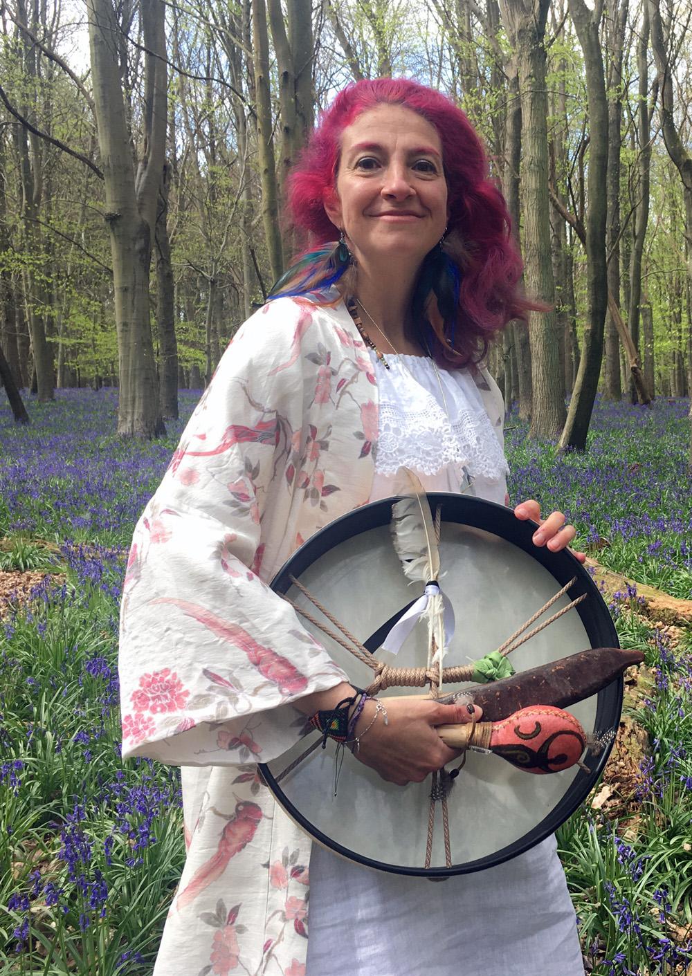 Gloria Urech holding medicine drum in the woods