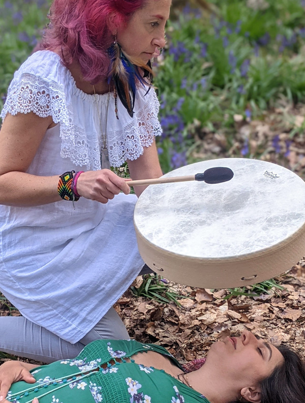Gloria Urech playing drum in the woods