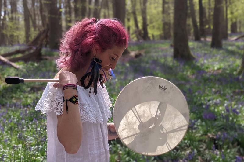 Gloria Urech holding drum in the woods